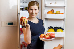 Healthy Eating Concept. Happy woman with apple standing at the opened fridge with fruits, vegetables and healthy food. Healthy Eating Concept. Happy woman with royalty free stock image