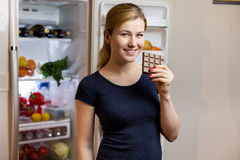 Healthy Eating Concept. Happy woman with chocolate bar standing at the opened fridge with fruits, vegetables and healthy Stock Photography