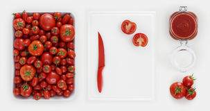 Healthy eating concept many fresh tomatoes with sauce in jar glass, cutting board on kitchen white worktop, copy space, top view royalty free stock images