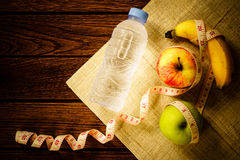 Healthy eating concept - tape measure, banana, apple, fruit and w Stock Photography