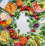 Healthy eating concept with various diet salad lunch boxes and ingredients around white cutting board, top view, frame. Clean orga Stock Images