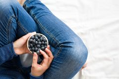 Healthy eating concept. Woman having blueberries in bed. stock image