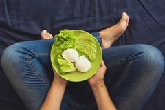 Healthy eating concept. Woman`s hands holding plate with lettuce, avocado slices and poached eggs. Top view stock photo