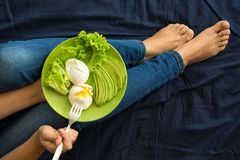 Healthy eating concept. Woman`s hands holding plate with lettuce, avocado slices and poached eggs. Top view Stock Photography