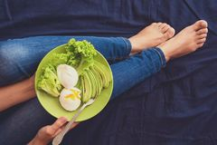 Healthy eating concept. Women`s hands holding plate with lettuce, avocado slices and poached eggs. Top view stock images