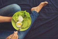 Healthy eating concept. Women`s hands holding plate with lettuce, avocado slices and poached eggs. Top view stock photography