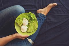 Healthy eating concept. Women`s hands holding plate with lettuce, avocado slices and poached eggs. Top view royalty free stock image