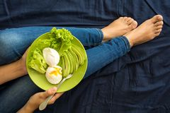 Healthy eating concept. Women`s hands holding plate with lettuce, avocado slices and poached eggs. Top view stock photos