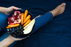 Healthy eating concept. Women`s hands holding plate with pears, grapes, persimmon and pomegranate fruits stock images