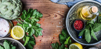 Healthy eating and cooking with fresh organic ingredients. Herbs,spices and olives oil on rustic wooden background. Top view, banner Stock Photos