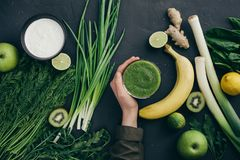 Healthy eating cooking green ingredients. Clean eating healthy cooking ingredients. Vegetables, beans, grains, greens, fruit, spices over grey marble background Royalty Free Stock Images