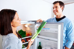 Healthy fridge couple. Healthy eating couple get fresh vegetables out of the fridge to cook food Royalty Free Stock Image