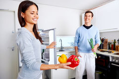 Healthy fridge couple. Healthy eating couple get fresh vegetables out of the fridge to cook food Stock Image