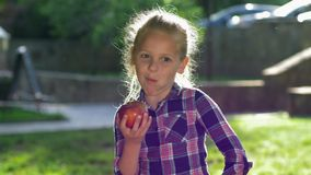 Healthy eating, cute small girl in checkered shirt bites and funny chew ripe juicy apple in backlight outdoors