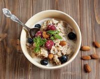 Healthy eating and diet concept: Oatmeal porridge in bowl topped with fresh blueberries and raspberries on wooden table. Oatmeal porridge in bowl topped with Royalty Free Stock Photo