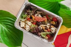 Healthy food in foil boxes, diet concept. Seafood salad Stock Image