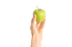 Healthy eating and diet Topic: Human hand holding a green apple isolated on a white background in the studio, first-person view Stock Images