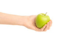 Healthy eating and diet Topic: Human hand holding a green apple isolated on a white background in the studio. Shot royalty free stock photo