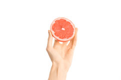 Healthy eating and diet Topic: Human hand holding a half of grapefruit isolated on a white background in the studio, first-person Stock Photos
