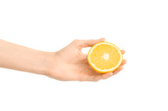 Healthy eating and diet Topic: Human hand holding a half of orange isolated on a white background in the studio Royalty Free Stock Images