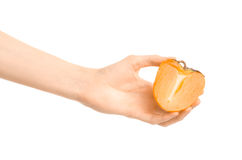 Healthy eating and diet Topic: Human hand holding a half of persimmons isolated on white background in the studio royalty free stock photography