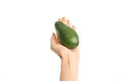 Healthy eating and diet Topic: Human hand holding a ripe avocado isolated on a white background in the studio, first-person view. Shot stock photography