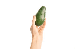 Healthy eating and diet Topic: Human hand holding a ripe avocado isolated on a white background in the studio, first-person view. Shot royalty free stock photo