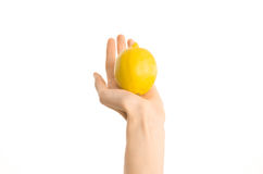 Healthy eating and diet Topic: Human hand holding yellow lemon isolated on a white background in the studio, first-person view Royalty Free Stock Photos