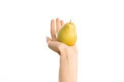 Healthy eating and diet Topic: Human hand holding yellow pear isolated on a white background in the studio, first-person view. Shot stock photos