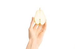 Healthy eating and diet Topic: Human hand holds half of pear isolated on a white background in the studio, first-person view. Shot stock photo