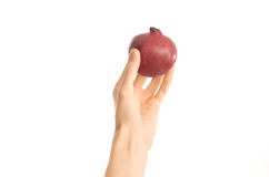 Healthy eating and diet Topic: Human hand holds a red pomegranate isolated on a white background in the studio, first-person view Royalty Free Stock Photo
