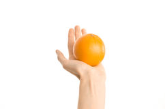 Healthy eating and diet Topic: Human hand holds a ripe orange isolated on a white background in the studio, first-person view Stock Photography