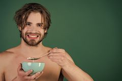 Healthy eating. Dieting and fitness, calorie. Man with wet hair eat breakfast on green background. Food and beauty, health. Sexy man with muscular body eating Stock Photography