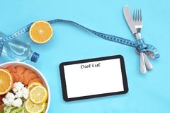 Healthy eating, dieting, slimming and weigh loss concept - close up of diet plan on tablet pc screen. royalty free stock image