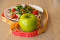 Healthy eating, dieting, slimming and weigh loss concept - close up of green apple, measuring tape and salad. Healthy eating, dieting, slimming and weigh loss Stock Photos