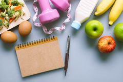Healthy eating, dieting, slimming and weight loss concept - Top. View of green and red apple, bananas, measuring tape, dumbbells, blank note book and vegetables Stock Photography