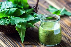 Healthy eating, drinks and diet concept. Beautiful appetizer green smoothie or spinach juice in glass jar with fresh leaves on woo. Den background, top view royalty free stock image