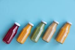Healthy eating, drinks, diet and detox concept - close up of five bottles with different fruit or vegetable juices for detox plan. royalty free stock photos