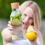 The girl is holding a detox drink from a lemon and mint with a cucumber on a background of green grass. Healthy eating, drinks, diet. The girl is holding a detox royalty free stock images