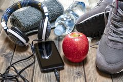 Healthy eating and equipment for leisure and outdoor sports, on rustic wooden background. Close-up of a red apple, sport shoes, audio headphone, smartphone Stock Photo