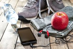 Healthy eating and equipment for leisure and outdoor sports, on rustic wooden background. Close-up of a red apple, sport shoes, audio headphone, smartphone Stock Images