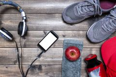 Healthy eating and equipment for leisure and outdoor sports, on rustic wooden background. Top view of a red apple, sport shoes, audio headphone, smartphone, hat Royalty Free Stock Image