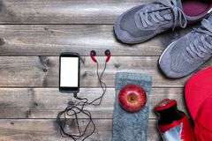 Healthy eating and equipment for leisure and outdoor sports, on rustic wooden background. Top view of a red apple, sport shoes, audio earphones, smartphone, hat Stock Photos