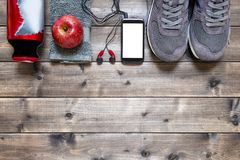 Healthy eating and equipment for leisure and outdoor sports, on rustic wooden background. Top view of a red apple, sport shoes, audio headphone, smartphone Stock Photo