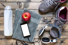 Healthy eating and equipment for leisure and outdoor sports, on rustic wooden background. Top view of a red apple, sport shoes, audio headphone, smartphone Royalty Free Stock Photos