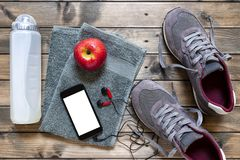 Healthy eating and equipment for leisure and outdoor sports, on rustic wooden background. Top view of a red apple, sport shoes, audio headphone, smartphone Stock Images