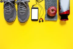 Healthy eating and equipment for leisure and outdoor sports, on yellow background. Top view of a red apple, sport shoes, audio headphone, smartphone, towel and Royalty Free Stock Photos
