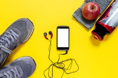 Healthy eating and equipment for leisure and outdoor sports, on yellow background. Top view of a red apple, sport shoes, audio headphone, smartphone, towel and Stock Images