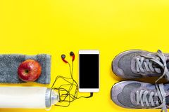 Healthy eating and equipment for leisure and outdoor sports, on yellow background. Top view of a red apple, sport shoes, audio headphone, smartphone, towel and Royalty Free Stock Images