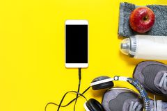 Healthy eating and equipment for leisure and outdoor sports, on yellow background. Top view of a red apple, sport shoes, audio headphone, smartphone, towel and Royalty Free Stock Image